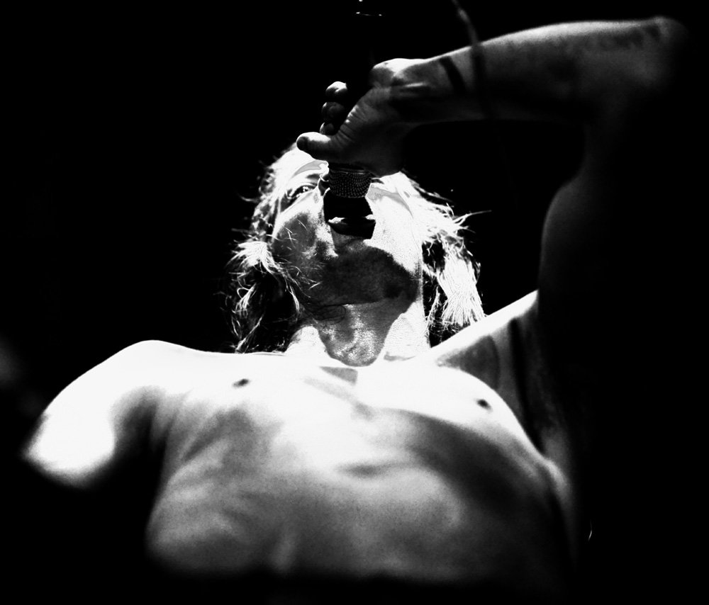 Shirtless Man holding a microphone